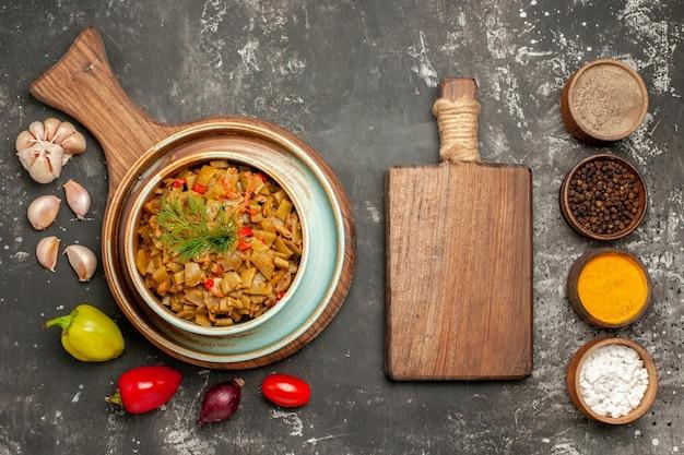 상단 클로즈업 보기 녹색 콩 흰색 노트북 접시에 토마토가 있는 녹색 콩 접시 피망 양파 마늘 절단 보드 및 어두운 테이블에 향신료 그릇