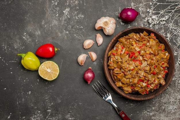 Vista ravvicinata dall'alto fagiolini con pomodori piatto di legno di fagiolini e pomodori accanto alla forchetta di aglio cipolla peperone limone sul tavolo