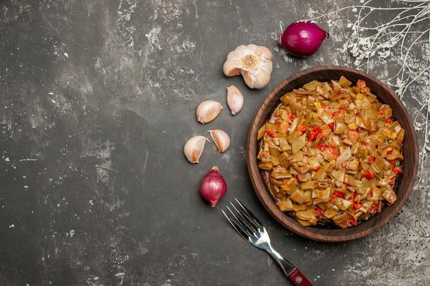 Vista ravvicinata dall'alto fagiolini con pomodori piatto di legno di fagiolini e pomodori accanto alla cipolla aglio e forchetta sul tavolo