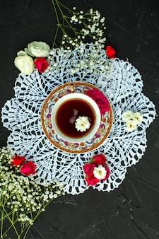 Una vista da vicino vista calda tè all'interno della tazza sul tessuto bianco sulla scrivania scura