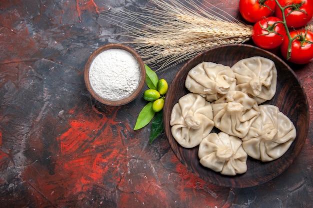 Top vista ravvicinata khinkali agrumi gustosa farina khinkali spighe di grano pomodori