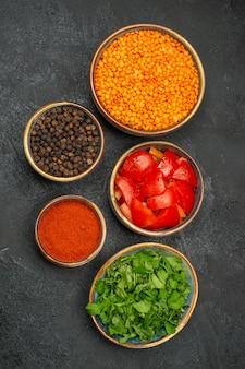 Top vista ravvicinata lenticchie ciotole di lenticchie pomodori spezie pepe nero erbe