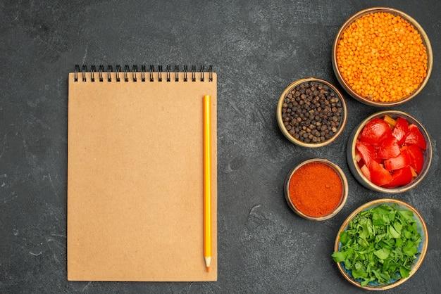 Сверху крупным планом чечевица чаши чечевицы травы помидоры черный перец специи тетрадь карандаш