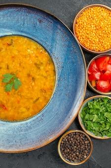 Top vista ravvicinata zuppa di lenticchie ciotola blu di zuppa di lenticchie pomodori spezie pepe nero erbe