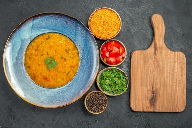 Top vista ravvicinata zuppa di lenticchie zuppa di lenticchie pomodori spezie le erbe del tagliere