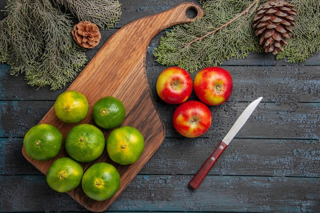 Top close-up view limes and apples seven green-yellow limes on the cutting board next to three apples knife and spruce branches and cones