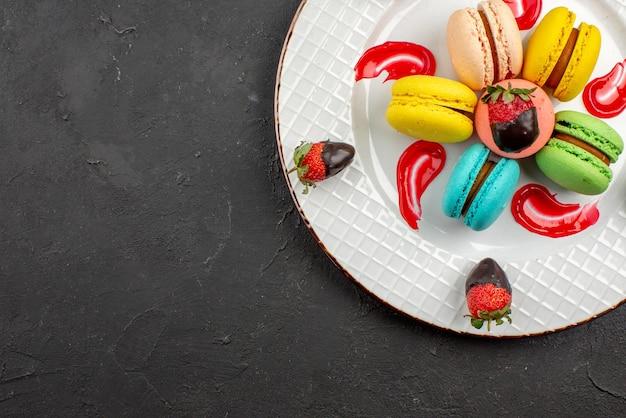 上のクローズアップビューマカロンカラフルなマカロンチョコレートで覆われたイチゴと暗いテーブルの右側にあるソース