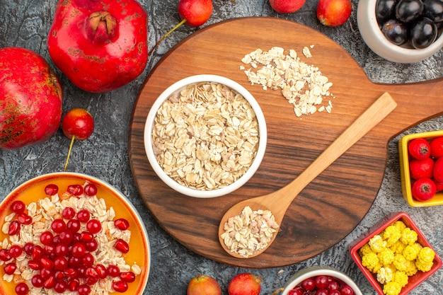 상위 확대보기 오트밀 보드에 식욕을 돋우는 석류 다채로운 열매 오트밀 숟가락