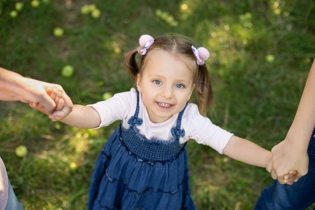 ジーンズのドレスを着た愛らしい 3 歳の子供の女の子を笑い、楽しんで公園の外の散歩を楽しんで、母親と祖母の手をつないで上から見る庭を散歩する家族。