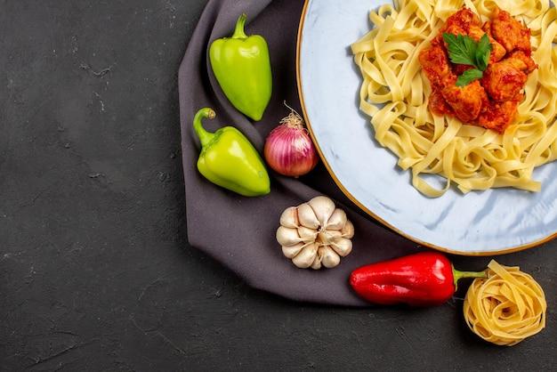 Вид сверху крупным планом макароны макароны мяч перец чеснок лук рядом с аппетитной пастой с мясом и подливкой на скатерти