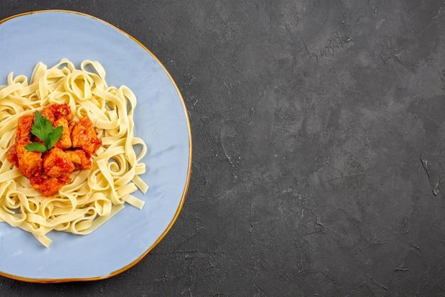Макароны с мясом сверху крупным планом, синяя тарелка аппетитных макарон с подливкой и мясом на левой стороне стола