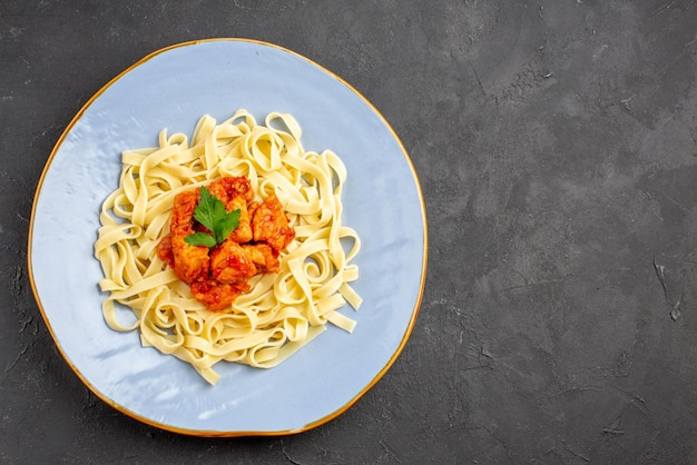 テーブルの左側に肉と肉汁が入った食欲をそそるパスタのミートプレートが付いた上部のクローズアップビューパスタ