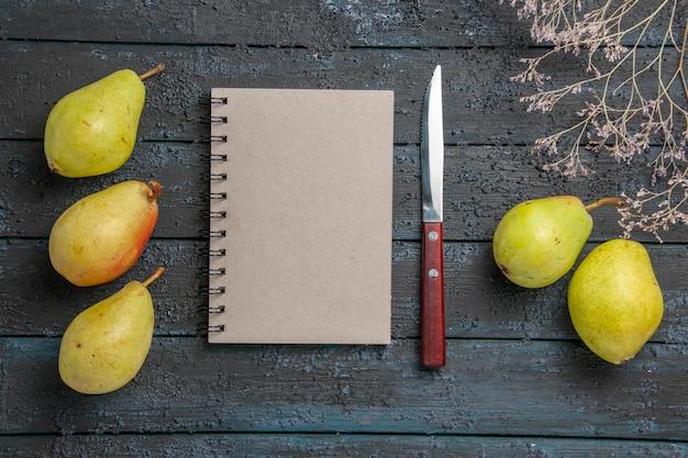 나무 가지 옆에 있는 식욕을 돋우는 배 사이의 상단 클로즈업 보기 배와 노트북 회색 노트북 및 칼