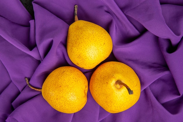 テーブルクロスの上のクローズアップビュー梨紫色のテーブルクロスの上の3つの食欲をそそる梨