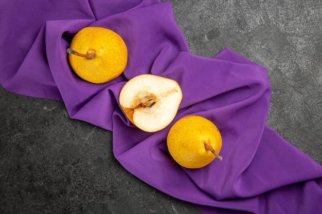テーブルクロスの上のクローズアップビュー梨2つの黄色の梨と暗いテーブルの紫色のテーブルクロスの半分の梨