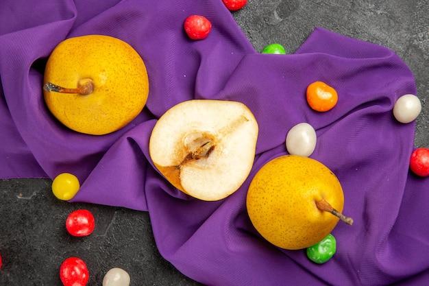 テーブルクロスの上のクローズアップビュー梨2つの黄色の梨半分の梨と暗いテーブルの紫色のテーブルクロスのカラフルなキャンディー