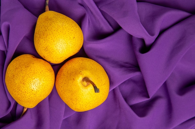Top close-up view pears on the tablecloth on the left side of the table three appetizing pears on the purple tablecloth