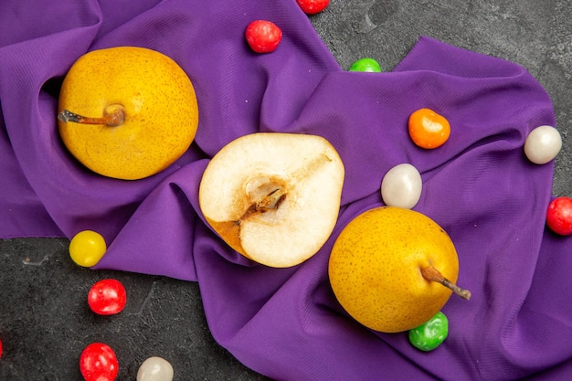 Vista ravvicinata dall'alto pere sulla tovaglia due pere gialle mezza pera e caramelle colorate sulla tovaglia viola sul tavolo scuro