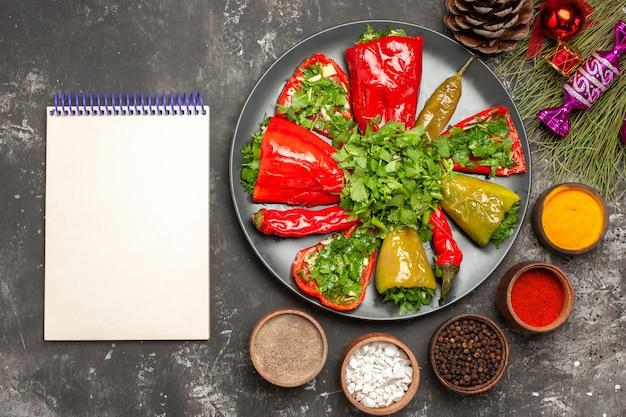 Top vista ravvicinata peperoni i peperoni appetitosi spezie cono notebook natale giocattoli rami di albero