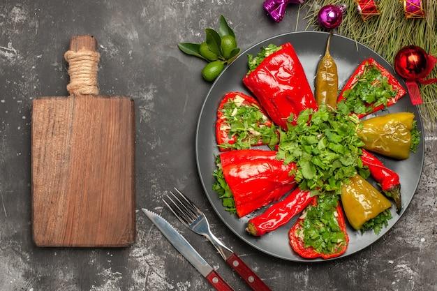 Top vista ravvicinata peperoni coltello forchetta piatto di peperoni albero di natale giocattoli il tagliere