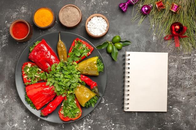 Top vista ravvicinata peperoni taccuino bianco piatto di peperoni albero di natale giocattoli spezie colorate