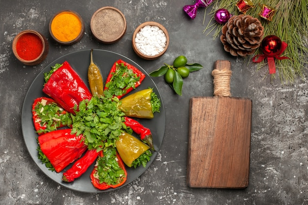 Top close-up view peppers wooden board plate of peppers christmas tree toys colorful spices