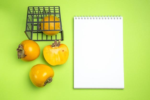 上部のクローズアップビュー柿灰色のバスケットノートの柿の隣に3つの柿