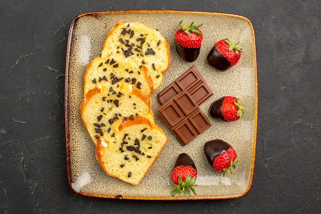 Top close-up view pieces of cake appetizing pieces of cake with chocolate and strawberries on dark table