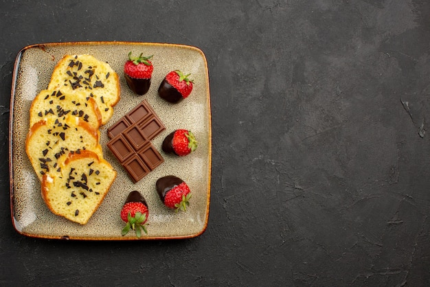 Top close-up view pieces of cake appetizing pieces of cake with chocolate and strawberries on the left side of dark table