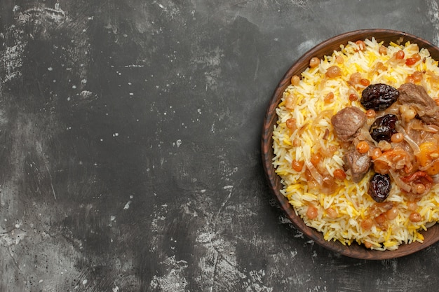 Vista ravvicinata dall'alto pilaf un appetitoso pilaf con frutta secca a base di carne nella ciotola marrone