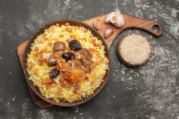 Vista ravvicinata superiore pilaf un appetitoso pilaf sulla cucina in legno bordo ciotola di aglio di riso