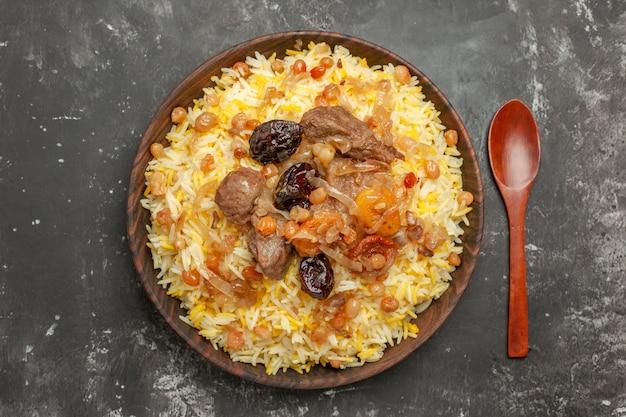 Вид сверху крупным планом плов сушеные фрукты рис и мясо в миске деревянной ложкой
