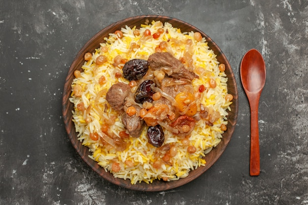 Top close-up view pilaf dried fruits rice and meat in the bowl wooden spoon