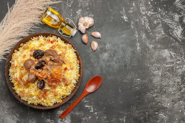 기름 나무 숟가락 식욕을 돋 우는 필라프의 상위 클로즈업보기 필라프 마늘 병