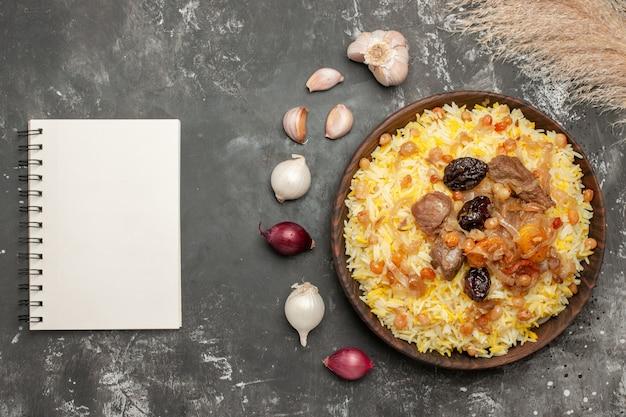 나무 그릇 노트북의 상위 근접 촬영보기 필라프 마늘 양파 식욕을 돋우는 필라프