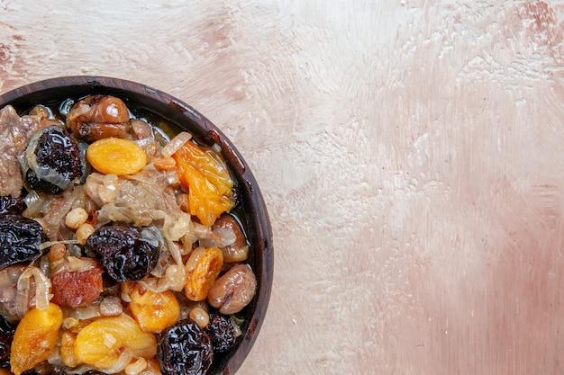 Vista ravvicinata superiore pilaf pilaf con frutta secca nella ciotola sul tavolo