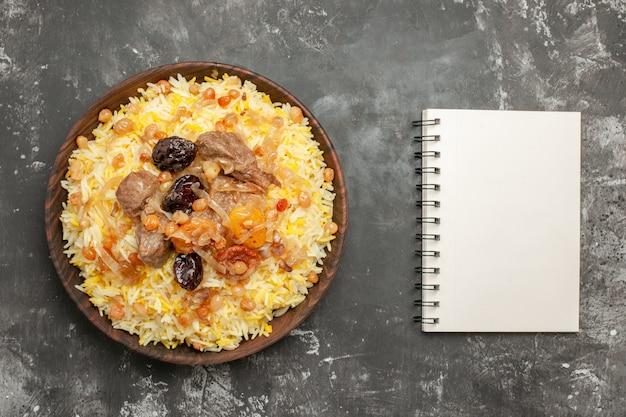 Vista ravvicinata superiore pilaf pilaf con carne di frutta secca nel taccuino bianco ciotola marrone