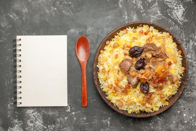Вид сверху крупным планом ложка для плова миска с рисовым мясом и записной книжкой с сухофруктами