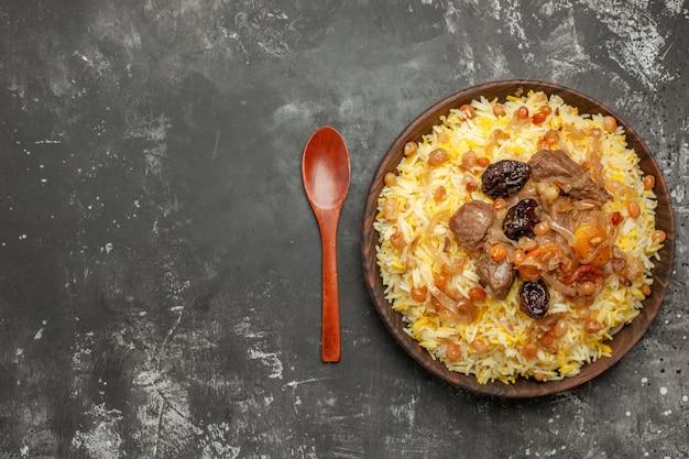 쌀 고기와 말린 과일의 상위 클로즈업보기 필라프 숟가락 그릇