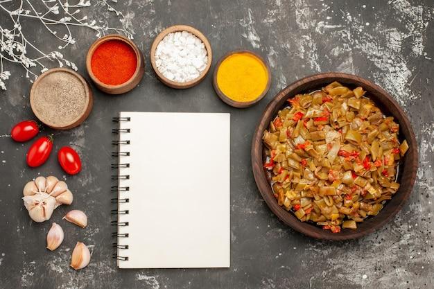 Vista ravvicinata dall'alto piatto di fagioli fagiolini pomodori accanto al quaderno bianco e ciotole di spezie colorate e aglio sul tavolo scuro