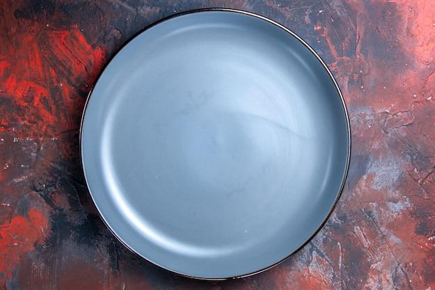 Piatto di vista ravvicinato dall'alto piatto rotondo blu su sfondo rosso-blu