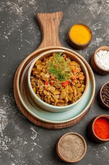 Vista ravvicinata dall'alto piatto di fagiolini piatto di fagioli accanto alle cinque ciotole di spezie diverse sul tavolo nero