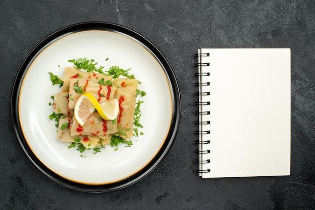 검은 표면에 있는 흰색 공책 옆에 있는 흰색 접시에 허브 레몬과 소스를 넣은 식욕을 돋우는 접시의 상단 클로즈업 보기 접시