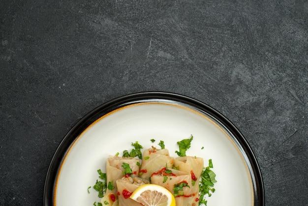 Верхний вид крупным планом тарелка аппетитного блюда голубцы с зеленью, лимоном и соусом на белой тарелке на черной поверхности