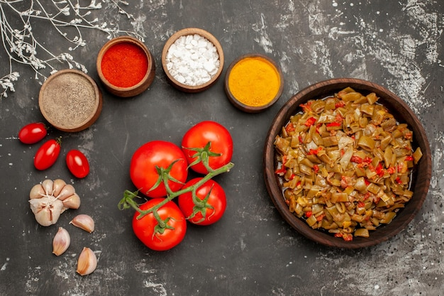 暗いテーブルの上のカラフルなスパイスニンニクのボウルの横に小花柄と豆緑豆トマトの上部のクローズアップビュープレート