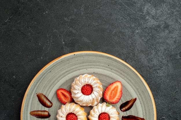 Верхняя тарелка с печеньем крупным планом, тарелка с аппетитным печеньем с шоколадом и клубникой на темном столе