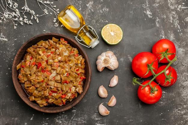 熟した赤いトマトの横にあるサヤインゲンのボトルのオイルガーリックレモンの上部の拡大図プレートとテーブル上のサヤインゲンとトマトのペディセルプレート