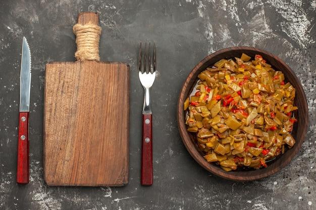 暗いテーブルのまな板ナイフとフォークの横にある食欲をそそるサヤインゲンとトマトの茶色のプレートのサヤインゲンの上部拡大図プレート