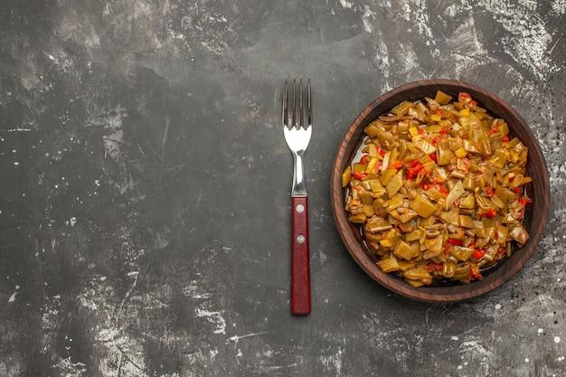 暗いテーブルの右側のフォークの横にある食欲をそそるインゲンとトマトの茶色のプレートの緑色の豆の上部のクローズアップビュープレート