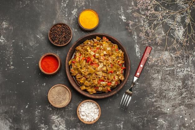 暗いテーブルの上のカラフルなスパイスとフォークのボウルの横にあるサヤインゲンとトマトのプレートの上部拡大図プレート